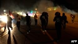 Фергюсон. Нааразылыкка чыккандарды полиция көздөн жаш агызчу газ менен атууда. 17-август.