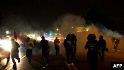 Клубы слезоточивого газа на месте разгона акции протеста в Фергюсоне, штат Миссури, США, 17 августа 2014 года.