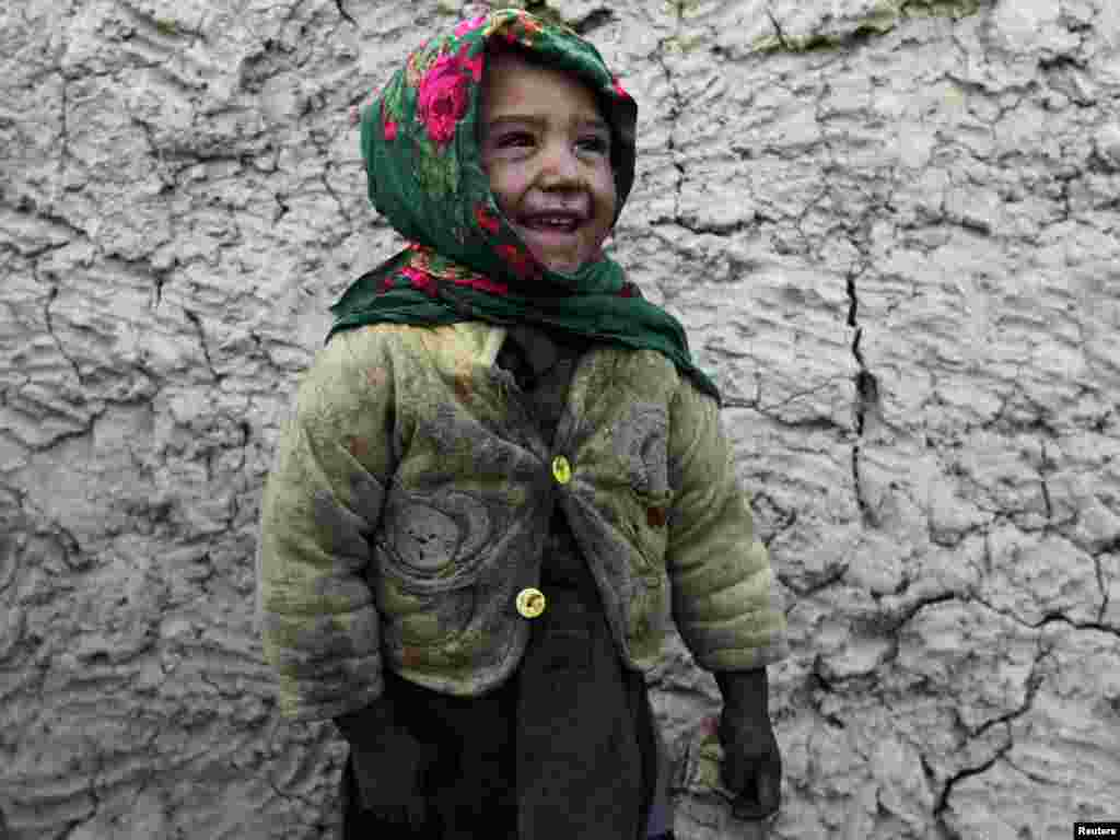 An internally displaced boy smiles in front of his residence in Kabul. Photo by Omar Sobhani for Reuters