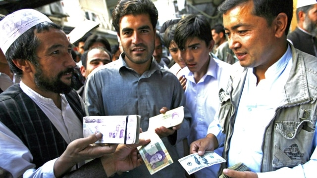 Money traders at a change market in Herat on October 4.