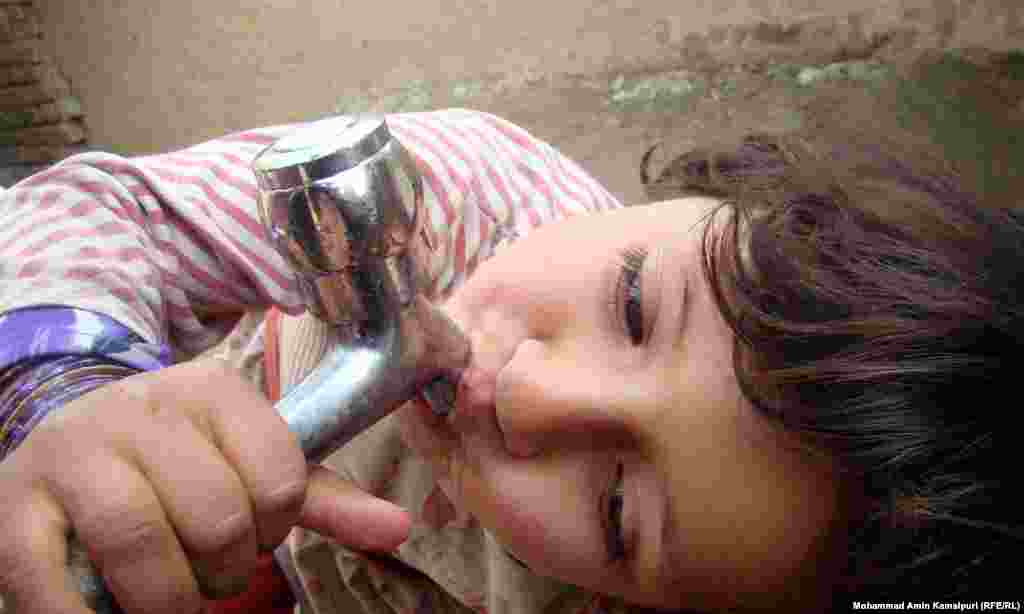 A child drinks from a tap at a camp for displaced people in Kabul.
