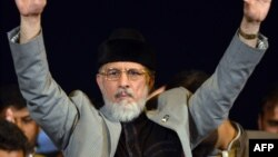 Tahir-ul-Qadri waves to supporters during an anti-government protest in front of the Parliament in Islamabad on August 27, 2014.