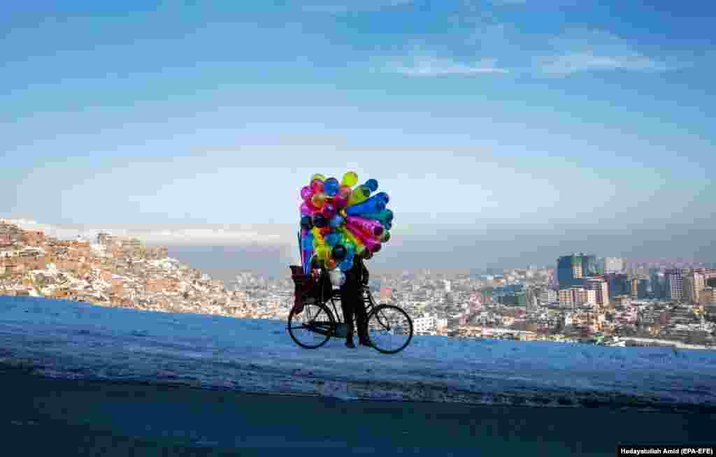 An Afghan balloon vendor looks for customers on a hilltop in Kabul. (epa-EFE/Hedayatullah Amid)