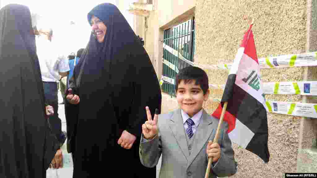 A boy with an Iraqi national flag and ink-stained finger after his mother casts her vote in Baghdad.