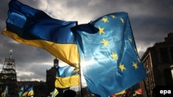 Ukraine -- Two men hold EU and Ukrainian flags during the pro-European protests rally on Independent Square in Kyiv, December 5, 2013