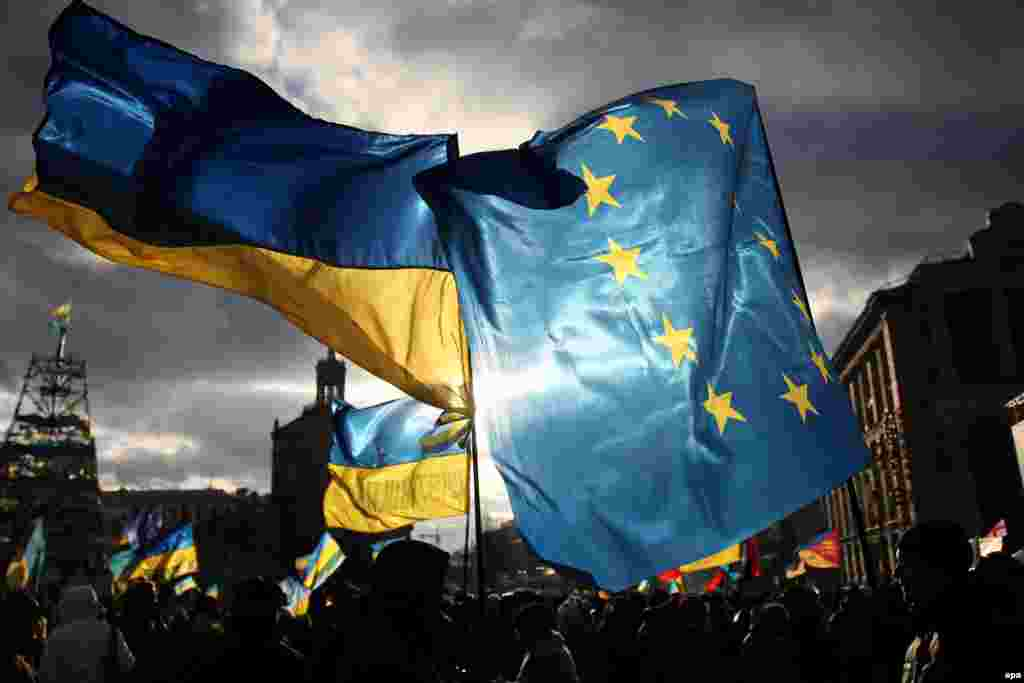 Two men hold EU and Ukrainian flags during a pro-European rally on Independence Square in Kyiv. (epa/Zurab Kurtsikidze)