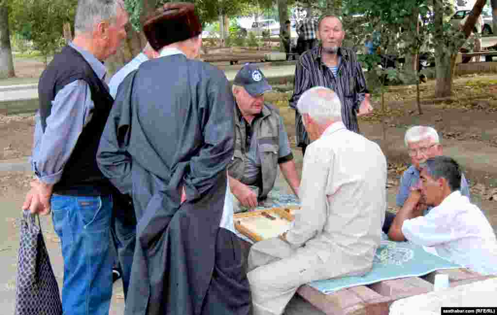 Türkmen ýaşululary dynç alyşda, açyk howada seçme oýnaýarlar. Beýleki ýaşulular bolsa oýna tomaşa edýärler.