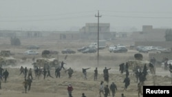 Protesters throw stones at Iraqi security forces during an antigovernment demonstration in Falluja on January 25.