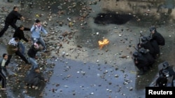 Antigovernment protesters clash with riot police at the Egyptian port city of Suez on January 27.