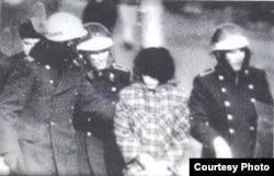 """Милиционеры ведут задержанную участницу Декабрьских событий 1986 года. Фотокопия снимка из книги Болатбека Толепбергенова """"Неизвестный Желтоксан""""."""