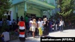 Aşgabatda, Türkmenistanyň döwlet ulaglar we aragatnaşyk institutynyň köne binasynyň okuw korpuslarynyň biriniň öňünde sanawa durmak üçin duran ýaşlar