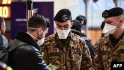Italian soldiers in Milan, Italy check train passengers on March 9.