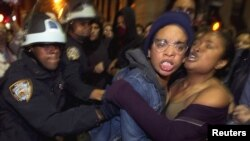 Members of the Occupy Wall Street movement clash with New York police after being removed from Zuccotti Park in New York on November 15.
