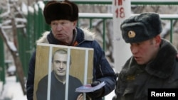 A man holds a portrait of jailed former oil tycoon Mikhail Khodorkovsky during a picket in support of Khodorkovsky outside the court building in Moscow where he was ordered to remain in jail until 2017.