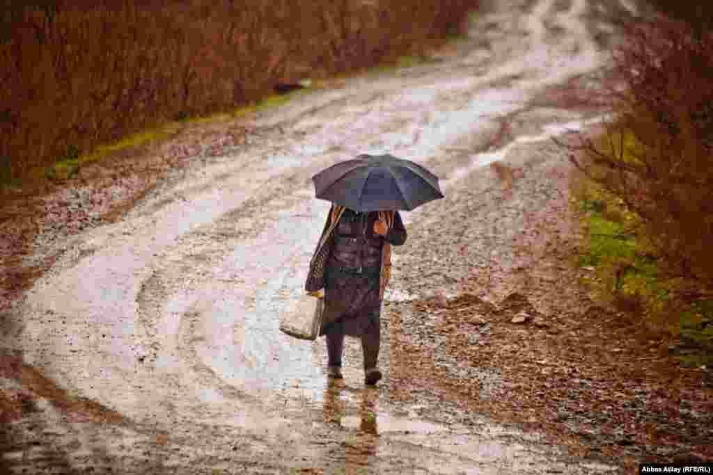 İmişli rayonunda yağış altında yol gedən qadın.