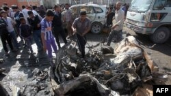 Iraqis inspect the site of a car bomb attack in Baghdad's impoverished district of Sadr City on February 17.