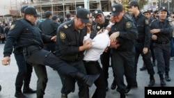 Полицейские задерживают участника оппозиционной демонстрации в Баку. Октябрь 2013 года.