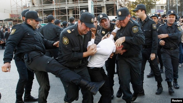 Police detain an opposition supporter in Baku in October 2013