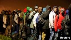 Migranti čekaju u redu na evakuaciju iz Kalea