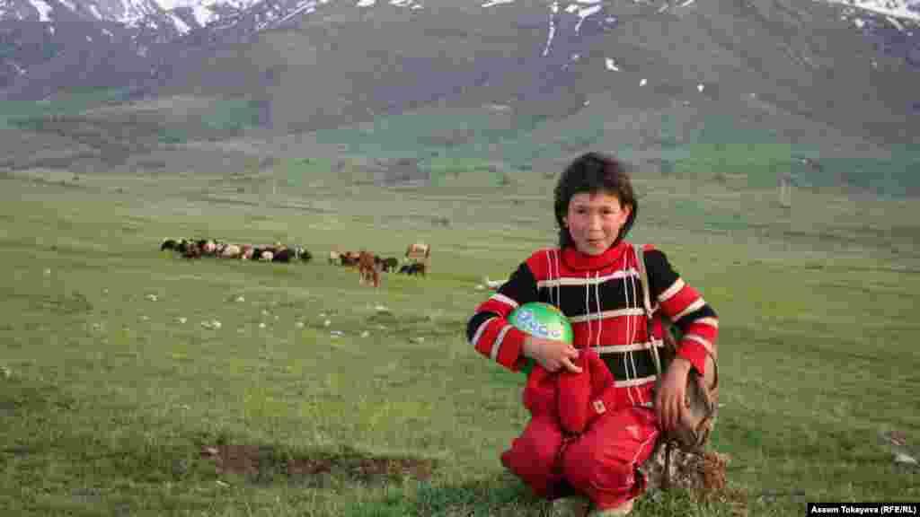 Местная девочка сидит на фоне гор в Аксу-Жабаглинском заповеднике.