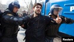 Полицейские задерживают участника акции протеста в Баку. 10 марта 2013 года.