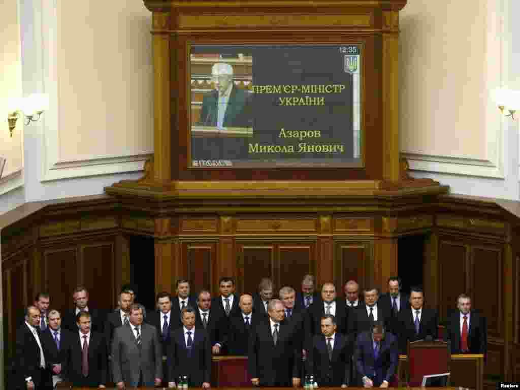 Члени нового Кабінету Міністрів стоїть під час складання присяги Прем'єр-міністром України Миколою Азаровим 11 березня
