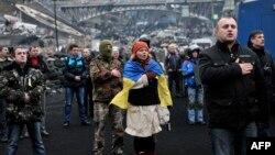 Участники антиправительственных протестов поют гимн на Майдане Незалежности в Киеве. 22 февраля 2014 года.