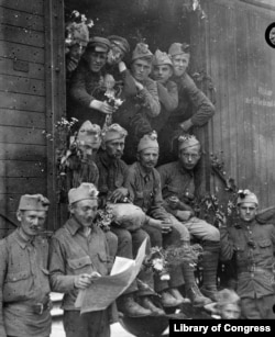 """Полските войски са транспортирани до фронтовата линия с камиони. Войниците получават """"цветя от полски момчета и момичета, докато минават""""."""