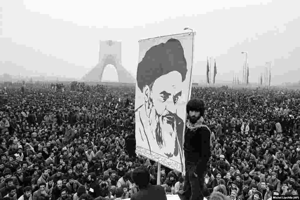 Demonstrators hold up a poster of exiled Islamic leader Ayatollah Ruhollah Khomeini as protests in Tehran grow larger. This anti-Shah demonstration on December 10, 1978 took place near the Shayah monument which was built to commemorate the monarch's rule and power.