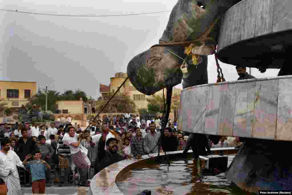 Иракчани влачат съборената статуя на иракския диктатор Садам Хюсеин в Кербала 18 дни след началото на войната в Ирак през 2003 г.