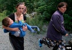 Осетинская семья в деревне Джава убегает от грузинского артобстрела. 8 августа 2008 года