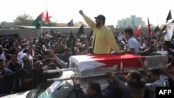 Protesters attend the funeral of Mahmud Mekki, who was killed during a raid on anti-regime protesters