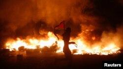 Палестинський протестувальник тримає національний прапор, 24 липня 2014