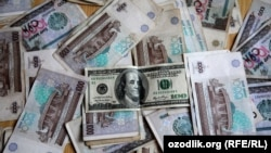 Узбекские сумы и американский доллар. Иллюстративное фото.