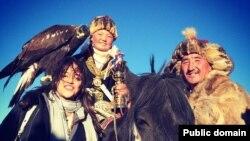 Девочка-беркутчи из Монголии Айшолпан Нургайып (в центре) со своей ловчей птицей.