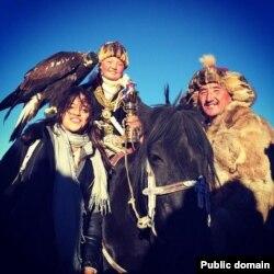 Моңғолиялық бүркітші қыз Айшолпан Нұрғайып (ортада) қыран құсымен.