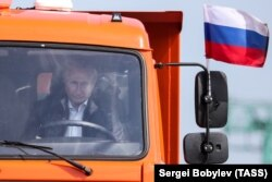 Putin driving the first truck over the Kerch Bridge to Crimea.