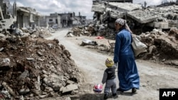 A Kurdish Syrian woman walks with her child past the ruins of Kobani after Islamic State militants had been pushed out of the town earlier this year.
