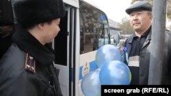Мужчина с синими шарами, которого полицейские препроводили к служебному автобусу для проверки документов. Астана, 22 марта 2018 года.