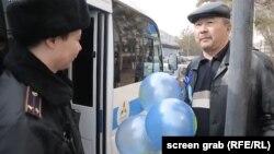 Көк шар ұстаған ер адам полиция машинасының жанында тұр. Астана, 22 наурыз 2018 жыл.