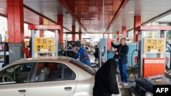 Iranian drivers refuel their vehicles at a gas station, on the first anniversary of the nuclear agreement, in the capital Tehran on Jaunary 14, 2017. - The first anniversary, of the nuclear deal between Iran and six powers, that lifted a large part of int