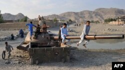 Совет танкісі қаңқасымен ойнап жүрген ауған балалары. Жалалабад, Ауғанстан, 16 қазан 2013 жыл.
