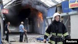 Пожарный на одном из местных рынков, пострадавшем в результате обстрела, Донецкая область, 3 июня 2015 года.