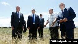 Армения - Премьер-министр Армении Овик Абрамян (второй слева) и министр сельского хозяйства Серго Карапетян (первый слева) на пшеничном поле, пострадавшем от сильного града, Ширакская область, 9 июля 2014 г.