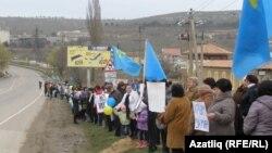 Женщины и дети стоят вдоль дороги в Крыму, держа в руках украинские и крымско-татарские флаги и плакаты с призывами к миру. 8 марта 2014 года.