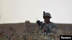Американский солдат идет через маковое поле близ афганской провинции Гильменд. Иллюстративное фото.