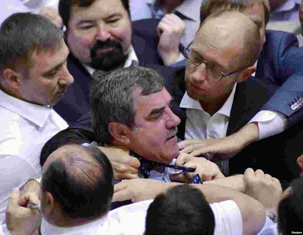 Ukrainian opposition leader Arseny Yatsenyuk (top right) holds the tie of a deputy from the pro-presidential Party of the Regions in Kyiv as opposition deputies attempted to disrupt a parliament session while demanding President Viktor Yanukovych deliver his state-of-the-nation address in person, rather than by text only. (Reuters)