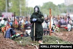 A gravedigger wearing a protective suit stands by a grave during the burial of a COVID-19 victim on the outskirts of Moscow on May 15.