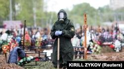 Работник похоронной службы в защитном костюме во время похорон жертвы COVID-19. Московская область, 15 мая 2020 года.