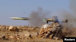 A rebel Free Syrian Army fighter fires an antitank missile in the eastern Hama region earlier this month.
